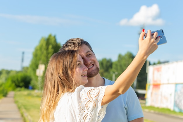 Schönes lustiges romantisches paar an naturwand. attraktive junge frau und hübscher mann machen selfie, lächeln und schauen in die kamera