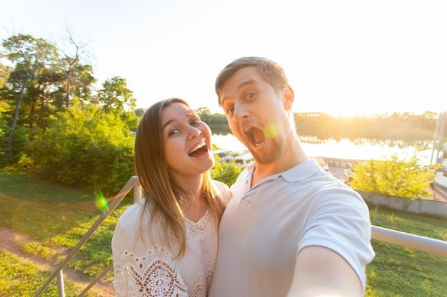 Schönes lustiges romantisches paar auf naturhintergrund. attraktive junge frau und gutaussehender mann machen selfie, lächeln und schauen in die kamera.