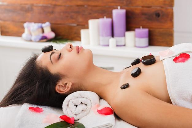 Schönes mädchen am steinmassage-spa im wellnesscenter