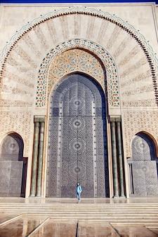 Schönes mädchen an der wand der hassan ii moschee in casablanca marokko
