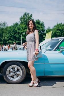 Schönes mädchen an einem sonnigen sommertag nahe einem auto