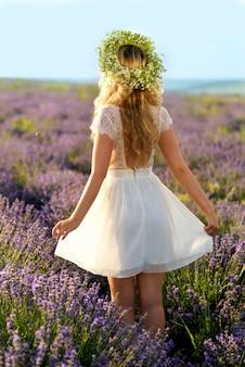 schönes mädchen auf dem lavendel gebiet. hübsche frau