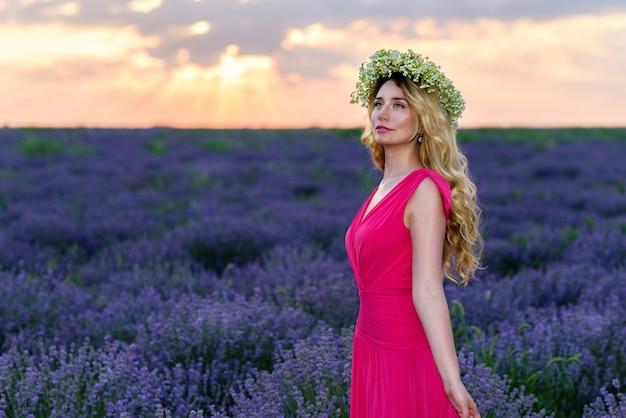Schönes mädchen auf dem lavendelgebiet bei sonnenuntergang im roten kleider- und blumenkranz