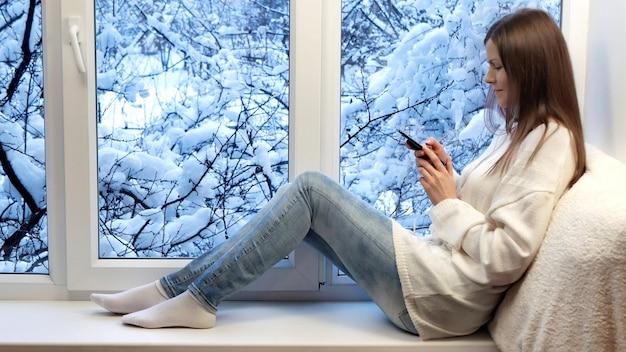 Schönes mädchen auf dem sitzenden fensterbrett, unter verwendung des smartphone. winter draußen.