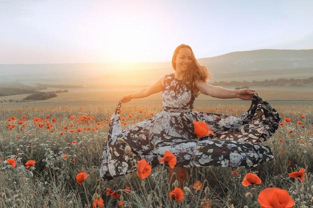 Schönes mädchen auf einem mohnblumengebiet bei sonnenuntergang. konzept der freiheit