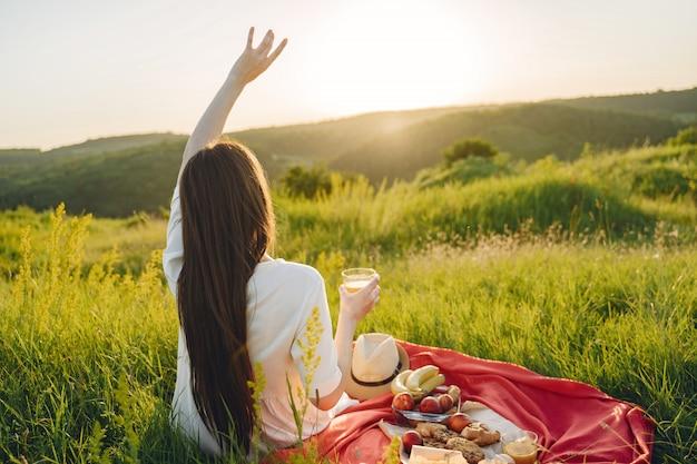 Schönes mädchen auf einem picknick im sommerfeld