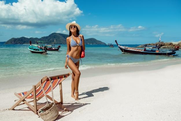 Schönes mädchen auf einer liege im bikini. tropischer urlaub. thailändische boote und blaues meer auf