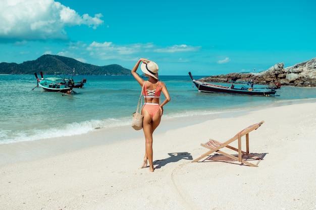 Schönes mädchen auf einer liege im bikini. tropischer urlaub. thailändische boote und blaues meer