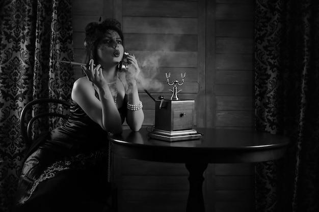 Schönes mädchen aus den 1930er jahren raucht eine zigarette am tisch