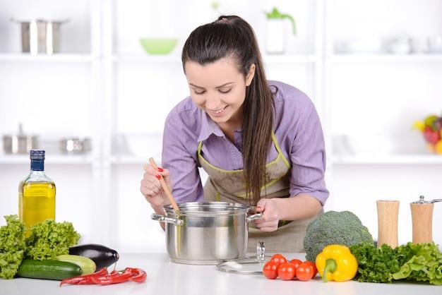 Schönes mädchen bereitet lebensmittel in der schönen küche zu.