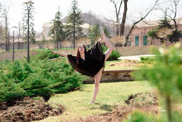 Schönes mädchen beschäftigt sich mit choreografie in der natur.