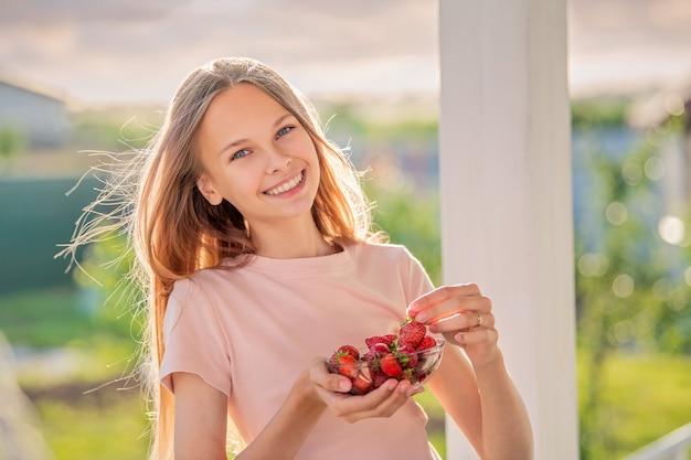 Schönes mädchen, blondine, teenager mit langen haaren an einem sommerabend isst erdbeeren auf der veranda