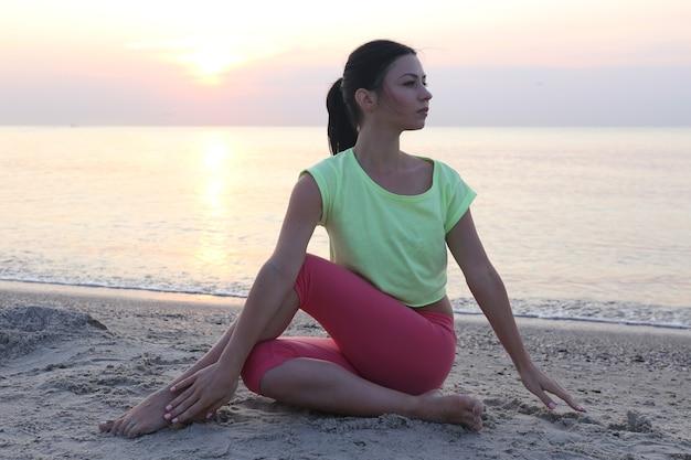 Schönes mädchen, das am morgen yoga am strand praktiziert
