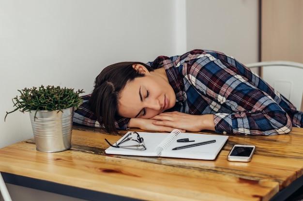 Schönes mädchen, das am tisch, vor notizbuch ein schläfchen hält