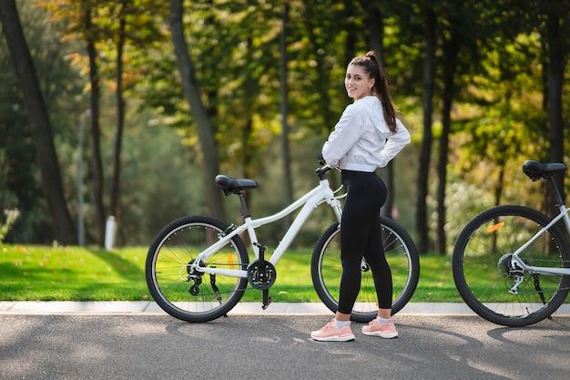 Schönes mädchen, das am weißen fahrrad aufwirft. spazieren sie in der natur.