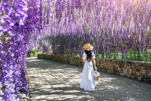 Schönes mädchen, das an lila blumentunnel in chiang rai, thailand geht