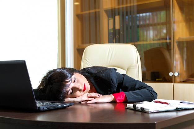 Schönes mädchen, das an seinem schreibtisch im büro schläft