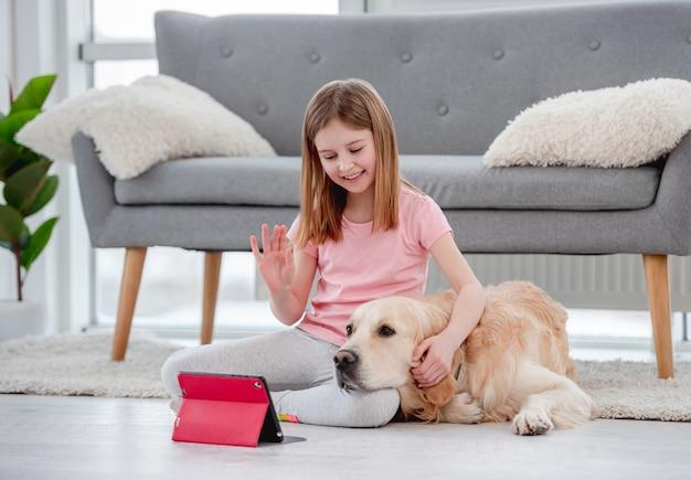 Schönes mädchen, das auf dem boden mit goldenem retrieverhund sitzt und mit familienfreunden online auf tablette spricht