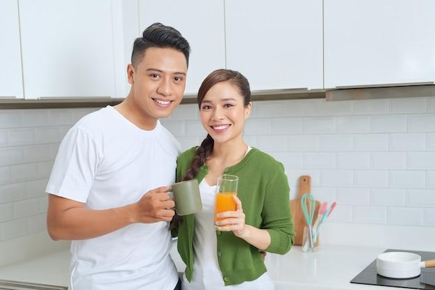 Schönes mädchen, das auf dem boden steht und mit freund spricht. junges paar, das kaffee in der küche genießt.