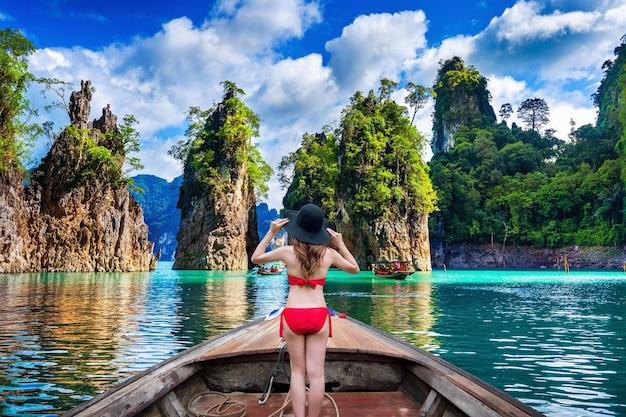 Schönes mädchen, das auf dem boot steht und zu den bergen in ratchaprapha dam bei khao sok nationalpark, surat thani provinz, thailand schaut.