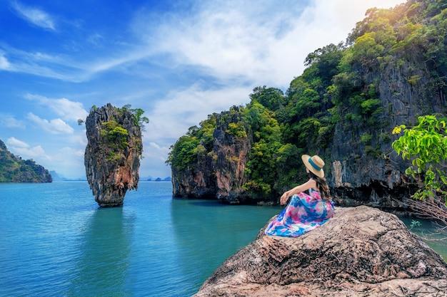 Schönes mädchen, das auf dem felsen bei james bond island in phang nga, thailand sitzt.
