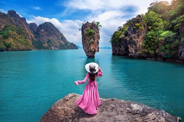 Schönes mädchen, das auf dem felsen bei james bond island in phang nga, thailand steht.