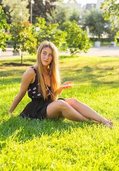 Schönes mädchen, das auf dem gras im park sitzt und musik hört.