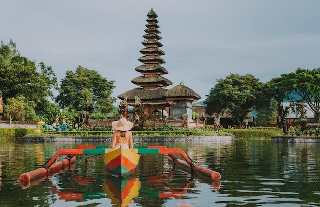 Schönes mädchen, das auf dem katamaran am ulun datu pura bratan tempel in bali kajak fährt