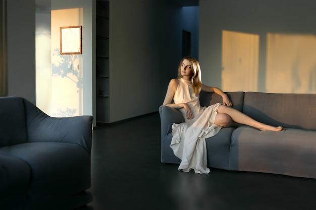 Schönes mädchen, das auf ein sofa in einem modernen wohnzimmer legt