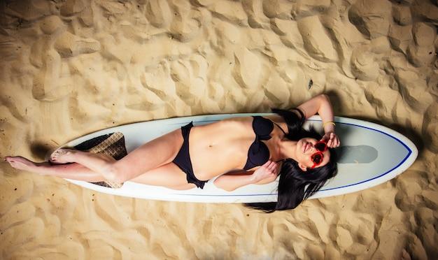 Schönes mädchen, das auf einem surfbrett am strand liegt