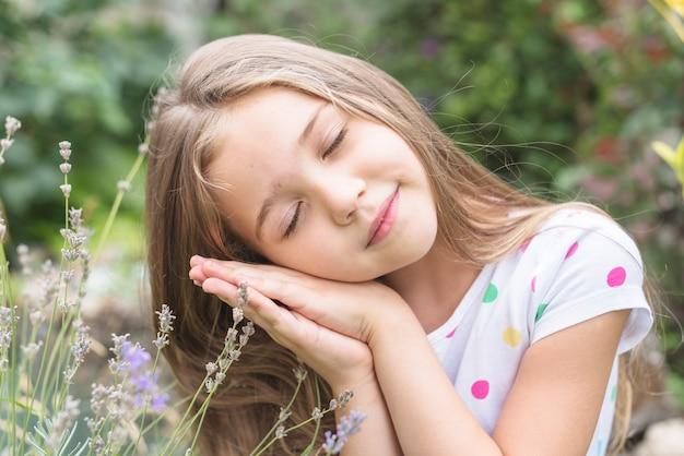 Schönes mädchen, das auf ihrer hand draußen schläft an sich sich lehnt