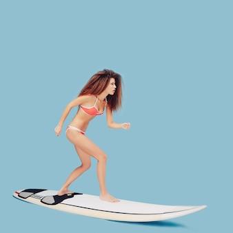 Schönes mädchen, das auf surfbrett steht