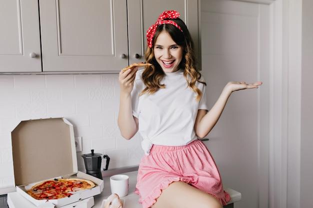 Schönes mädchen, das auf tisch in der küche mit stück pizza sitzt. herrliche lockige frau, die spaß während des abendessens hat und fastfood isst.