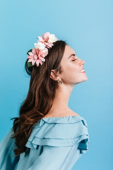 Schönes mädchen, das aufrichtig auf isolierter wand lächelt. modell in der krone der blumen, die für porträt im profil aufwerfen.