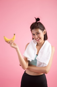 Schönes mädchen, das bananen nach übung isst, um gewicht zu steuern