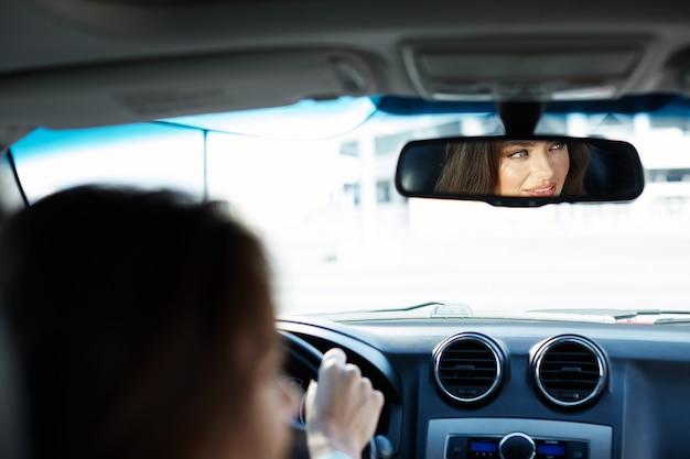 Schönes mädchen, das blaues hemd sitzt, das im neuen automobil sitzt, im verkehr stecken, porträt, neues auto kaufend, fahrerin.