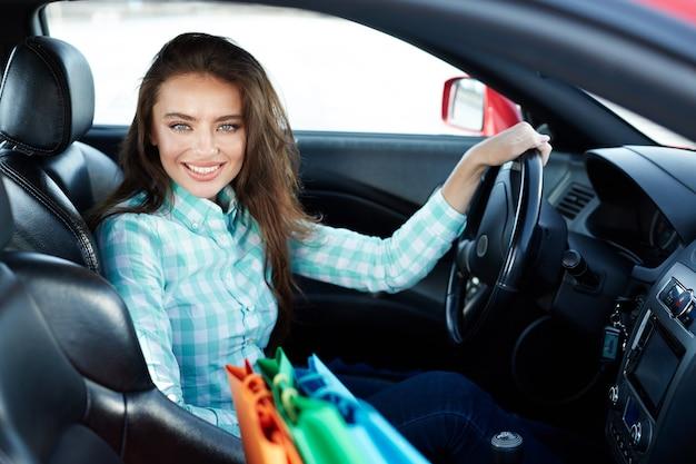 Schönes mädchen, das blaues hemd sitzt, sitzt in neuem automobil, steckt im verkehr, porträt fest, kauft neues auto, fahrerin, einkaufstaschen auf einem sitz, einkaufen.