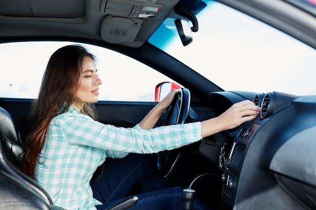 Schönes mädchen, das blaues hemd trägt, das im neuen auto sitzt, glücklich, im verkehr stecken bleibt, musik, porträt, fahrerin hört.