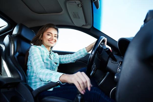 Schönes mädchen, das blaues hemd trägt, das im neuen automobil sitzt, glücklich, im verkehr stecken bleibt, musik hört, porträt, kamera betrachtet und lächelt.