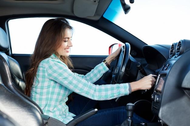 Schönes mädchen, das blaues hemd trägt, das im neuen automobil sitzt, glücklich, im verkehr stecken bleibt, musik hört, porträt.
