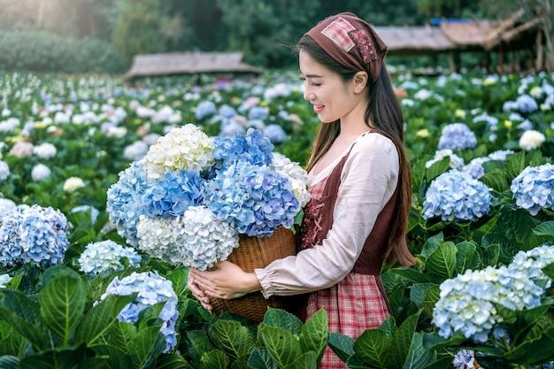 Schönes mädchen, das blühende blaue hortensienblumen im garten, chiang mai, thailand genießt