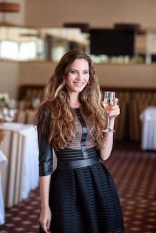Schönes mädchen, das champagner im restaurant trinkt.