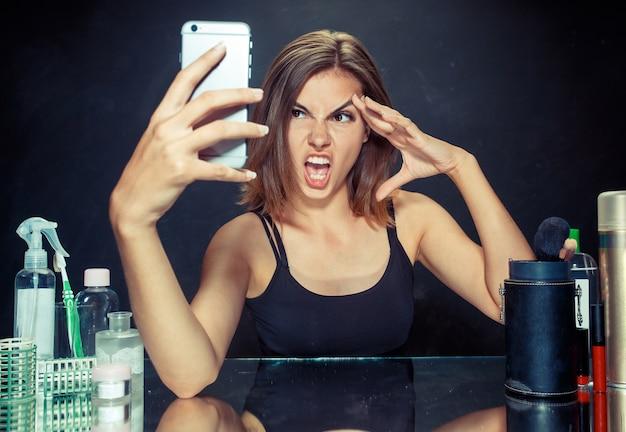 Schönes mädchen, das das handy betrachtet und selfie-foto macht