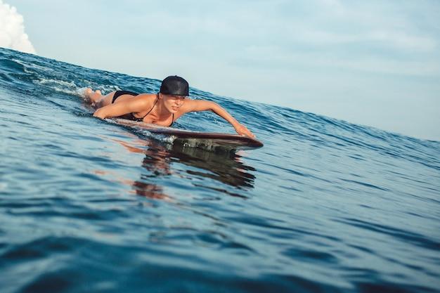 Schönes mädchen, das das sitzen auf einem surfbrett im ozean aufwirft