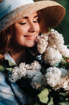Schönes mädchen, das den geruch von flieder an einem sommertag genießt. aromatherapie und frühlingskonzept.