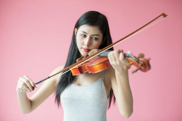 Schönes mädchen, das die violine auf rosa hintergrund spielt
