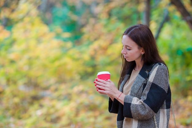Schönes mädchen, das draußen heißen kaffee im herbstpark trinkt