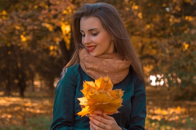 Schönes mädchen, das ein ahornblatt in der handnahaufnahme lächelt und hält
