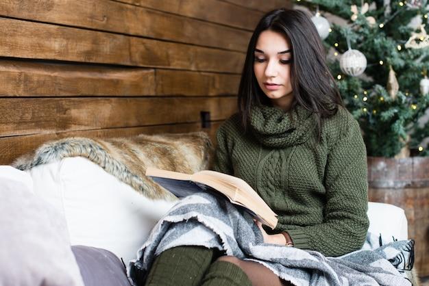 Schönes mädchen, das ein buch in einer weihnachtsatmosphäre liest
