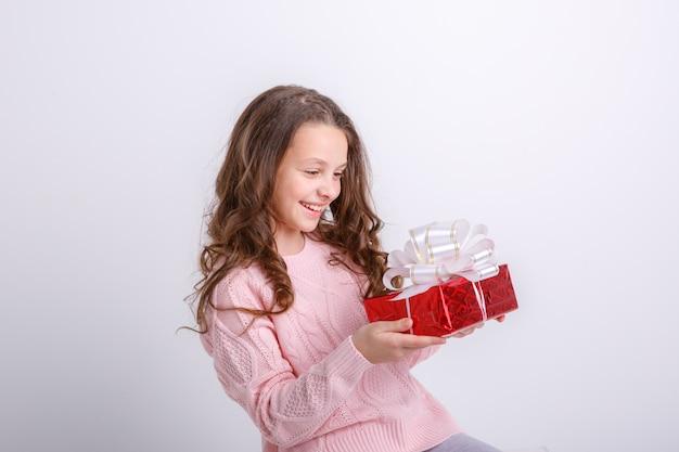 Schönes mädchen, das ein geschenk in ihren händen hält